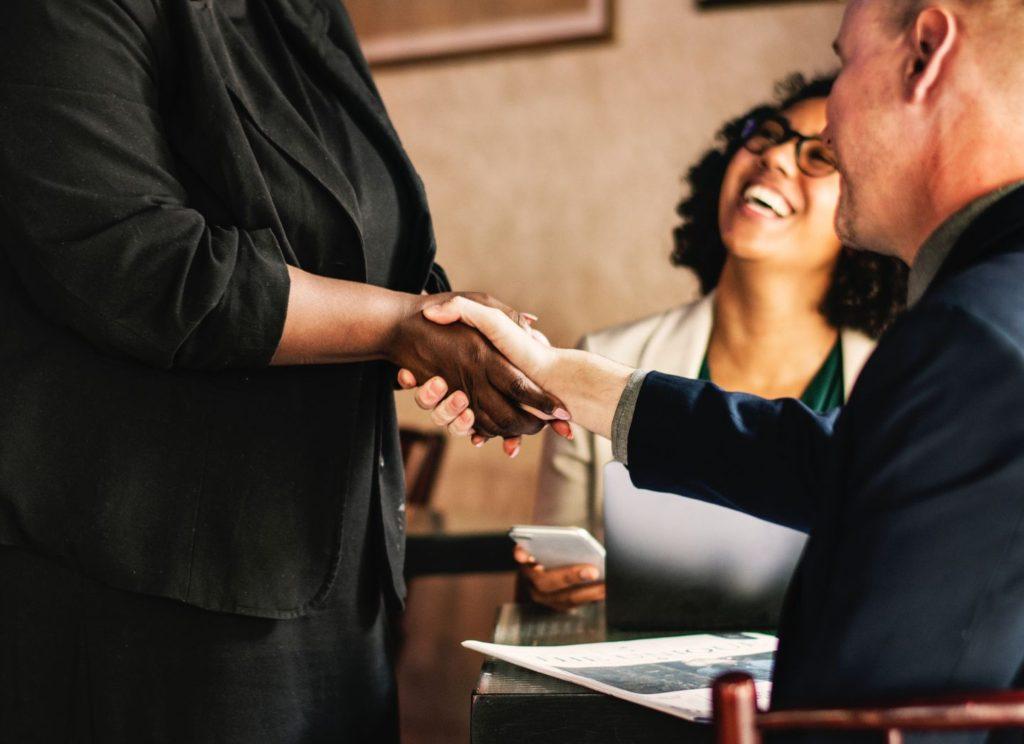 Immagine che mostra una donna sorridente proprietaria di un'azienda con una buona reputazione aziendale.