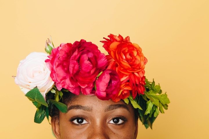 black girl face with garland of flowers