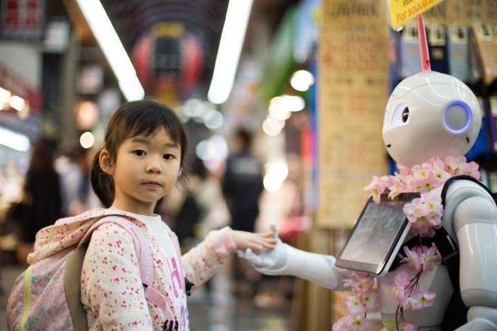 child holding the hand of a robot